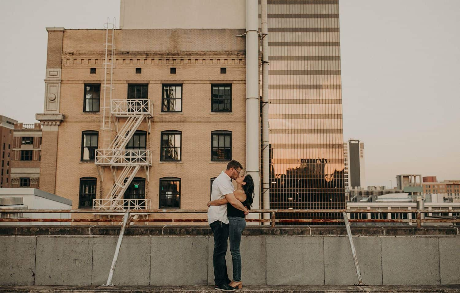 A man and woman hug and kiss on a rooftop overlooking a brick building with a fire escape