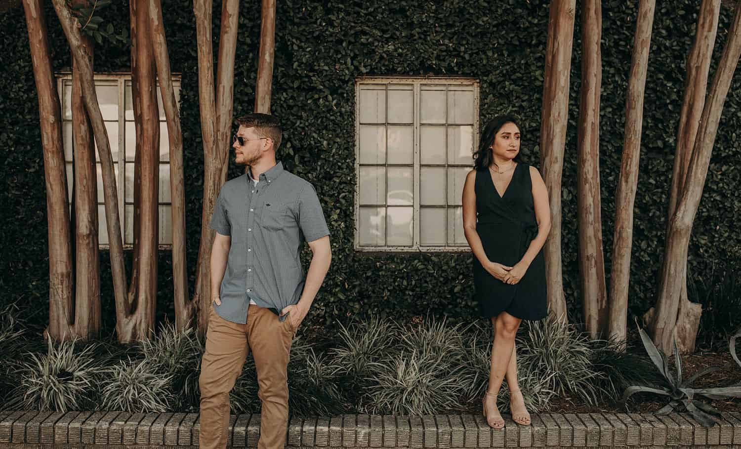 A tall man stands in front of a shady building looking to his right while a petite woman stands on a ledge above him looking to her left