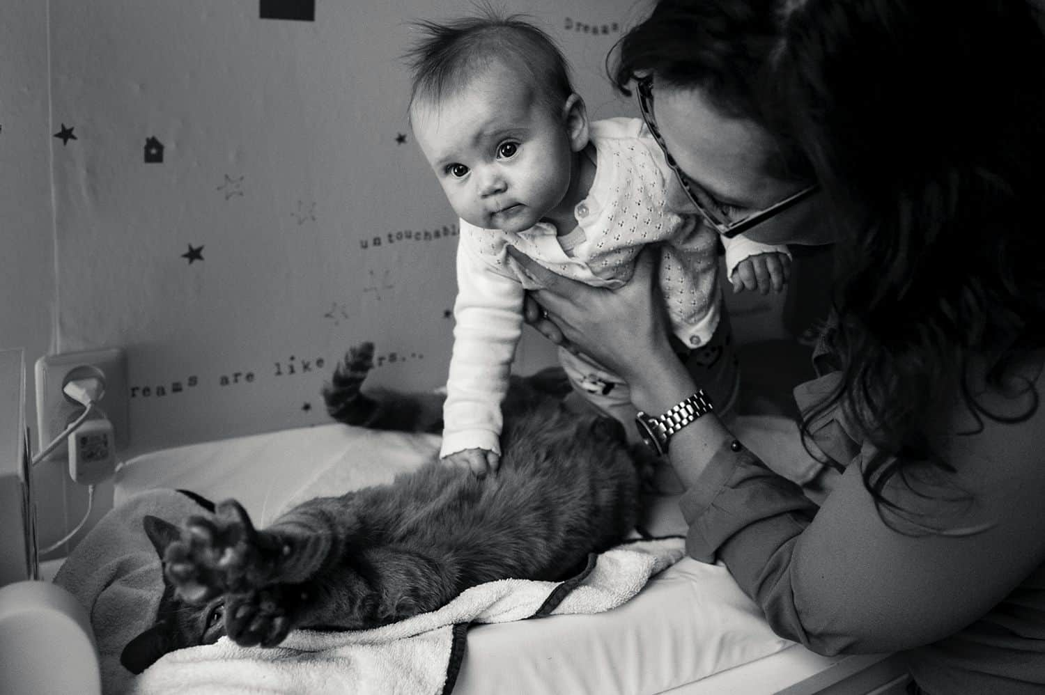 A mom holds her baby over the family cat so the child can pet the animal