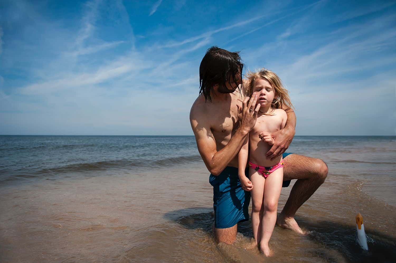 A dad wipes sunscreen on his little girl's face at the lake water's edge