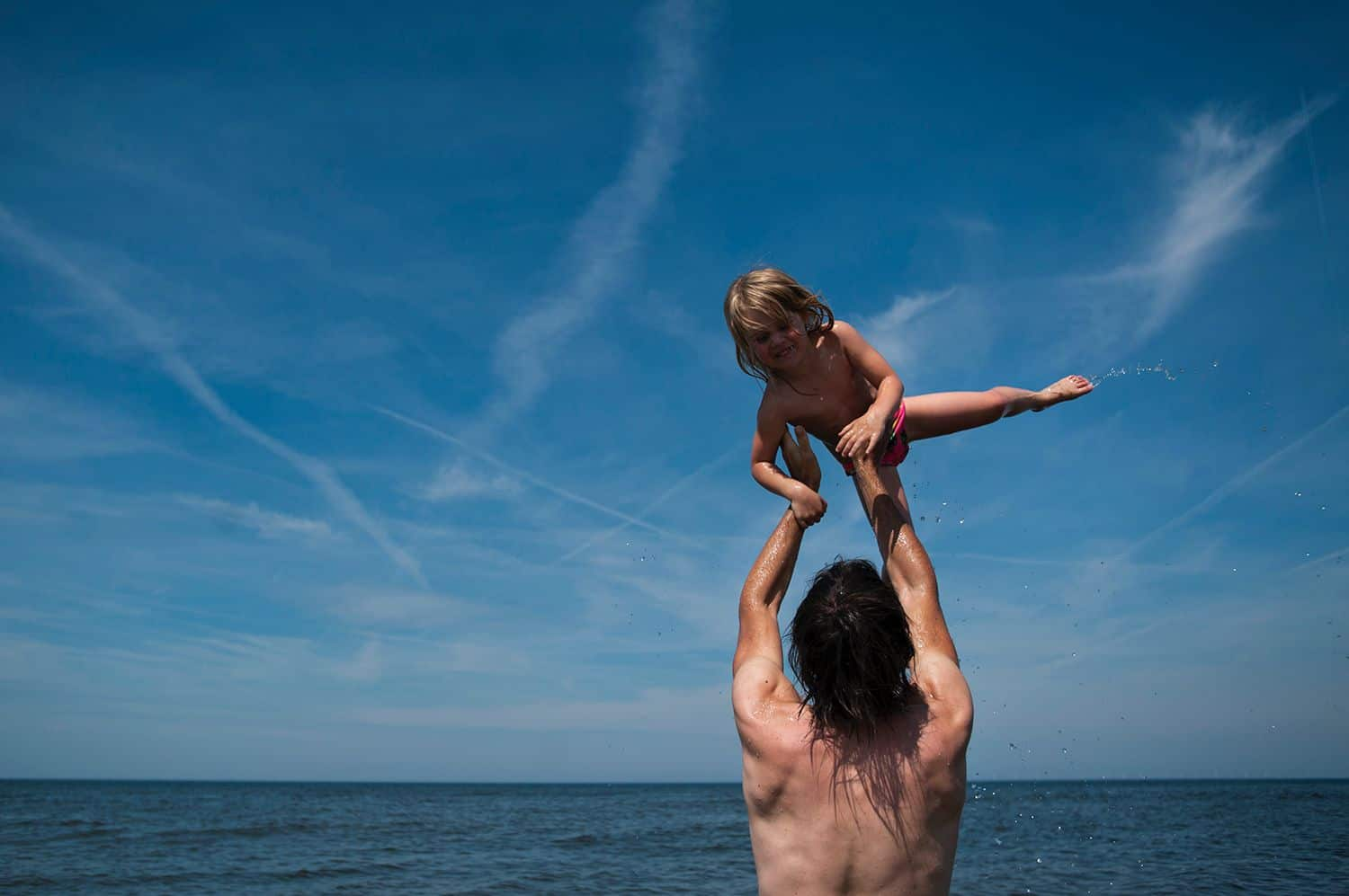 A shirtless dad tosses his young child into the blue sky above a lake