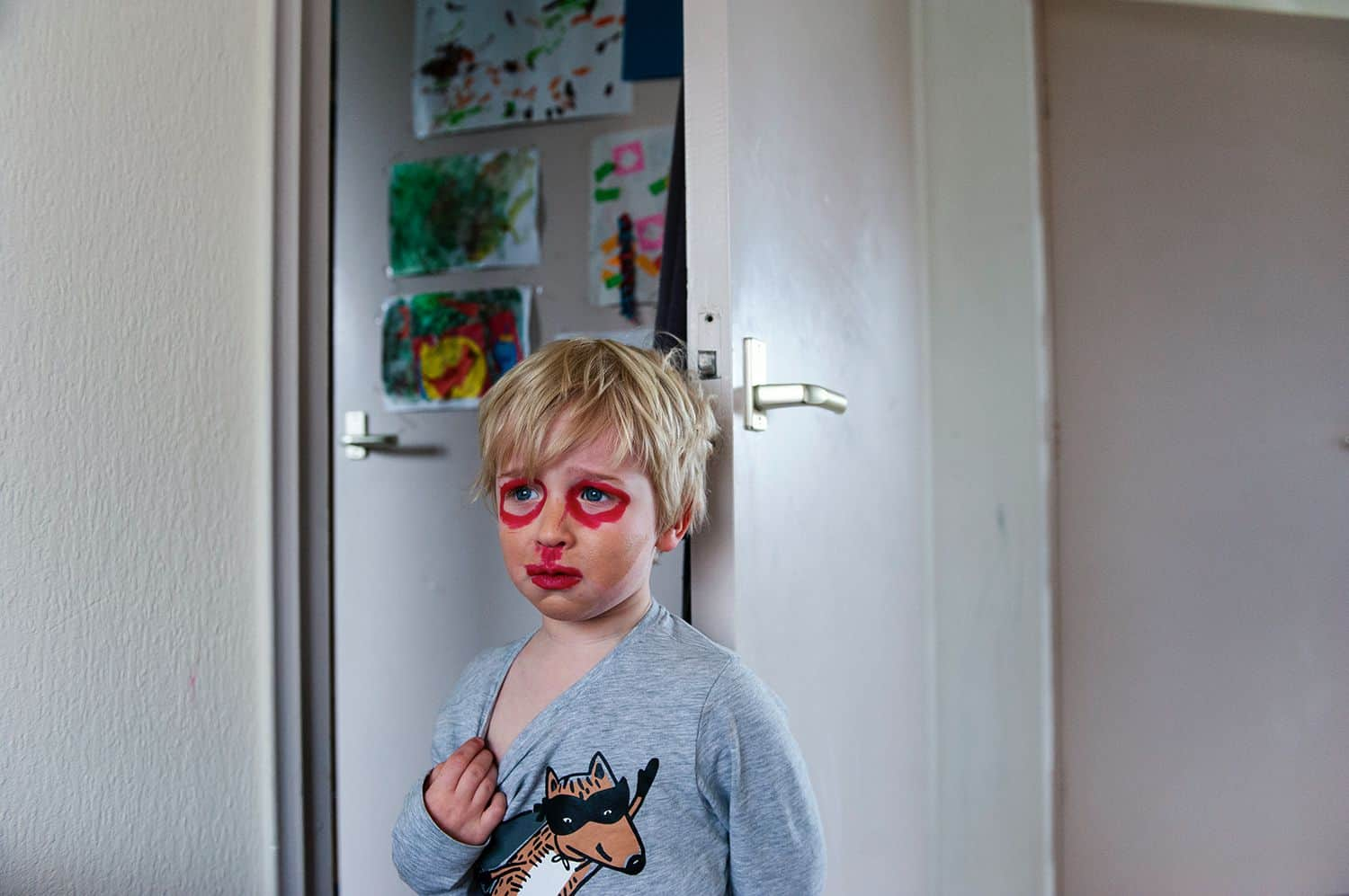 A little boy tugs at the neck of his sweatshirt looking distressed as he stands in a kitchen wearing self-applied makeup