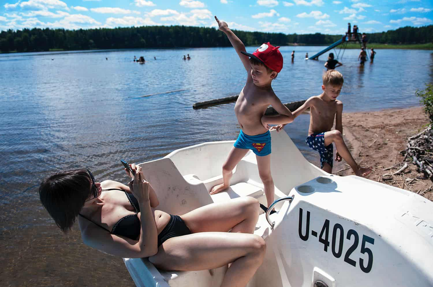 A little boy in a Superman bathing suit poses for his mom while standing on a peddle boat at the lake