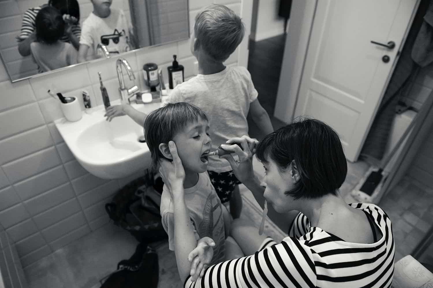 A mom brushes her younger child's teeth while her older child rinses their mouth at the sink