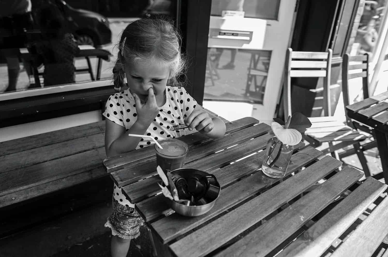 A little girl with a braid sits at an outdoor dining table picking her nose