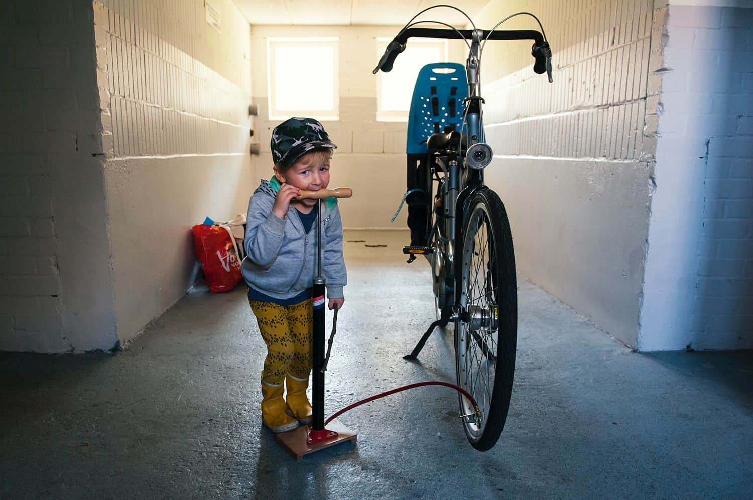 A little boy rests his mouth on the handle of the air pump he's using to inflate his bicycle tire