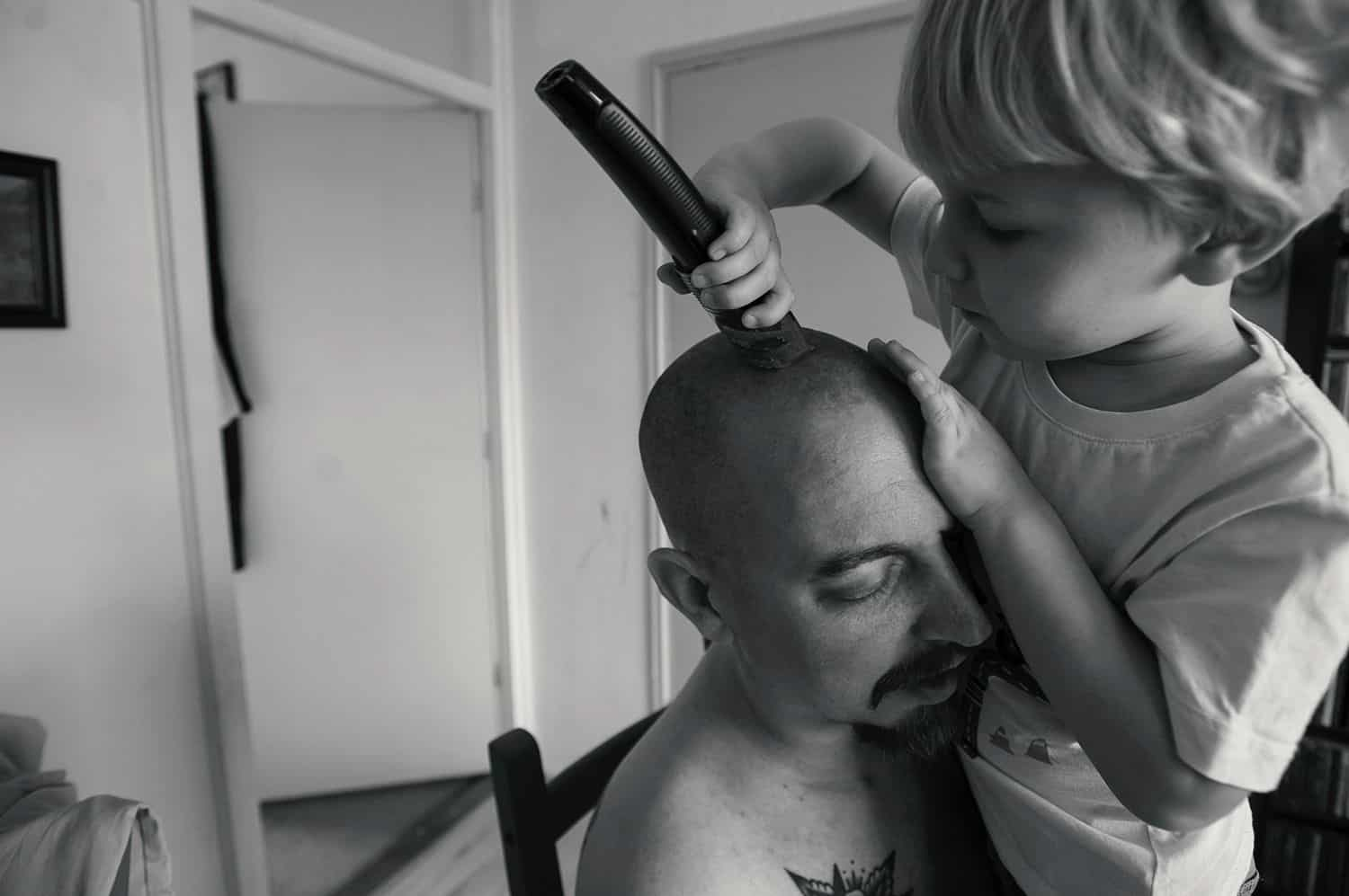 A dad holds his little boy close as the child shaves his father's dead with electric clippers