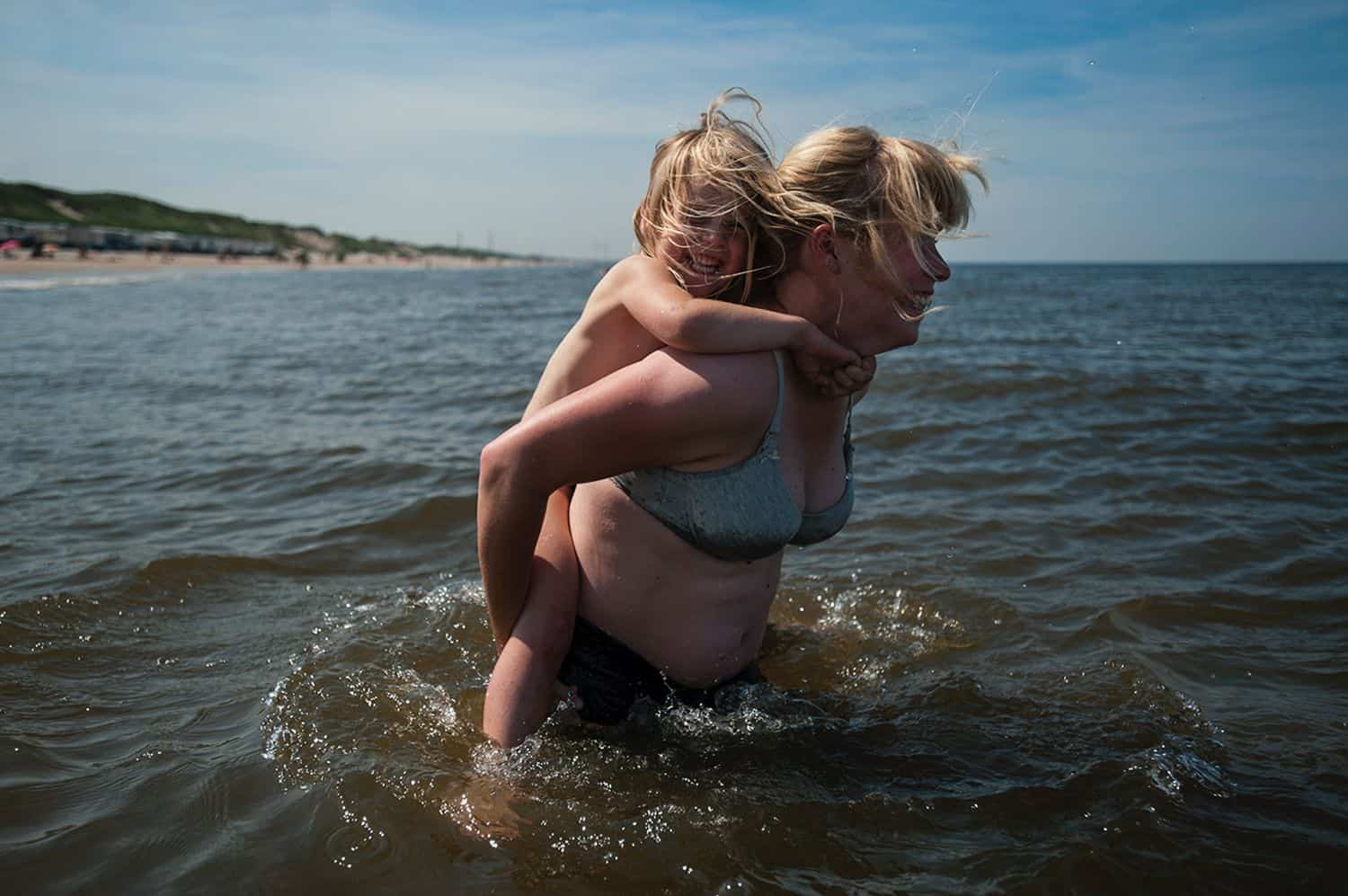 A mom carries her young child on her back through waist-deep lake water