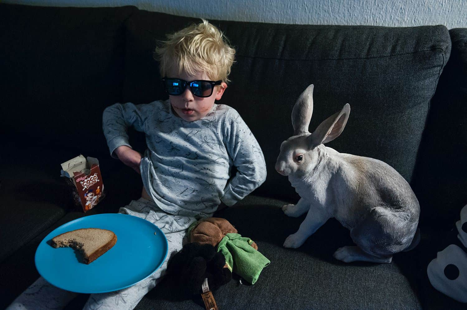 A little boy in sunglasses sits on a sofa eating a piece of bread with a rabbit statue sitting beside him