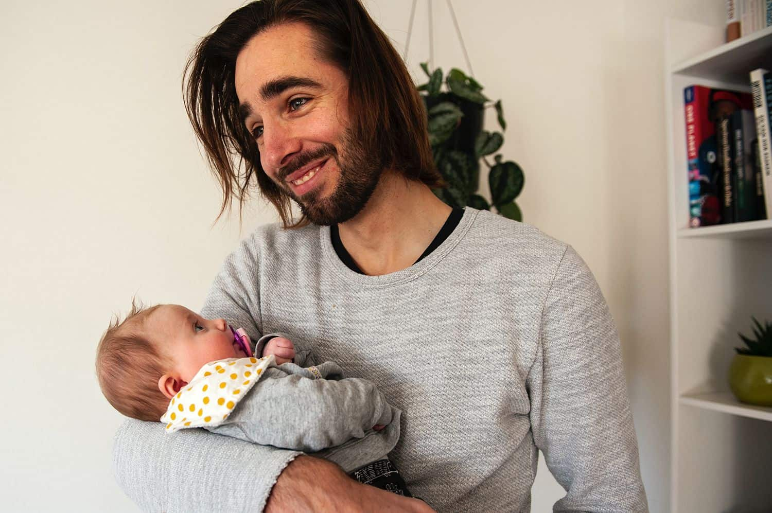 A dad smiles while holding his young baby who is sucking on a pacifier