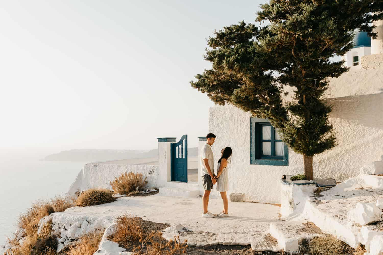 A couple stands on a cliff in Greece