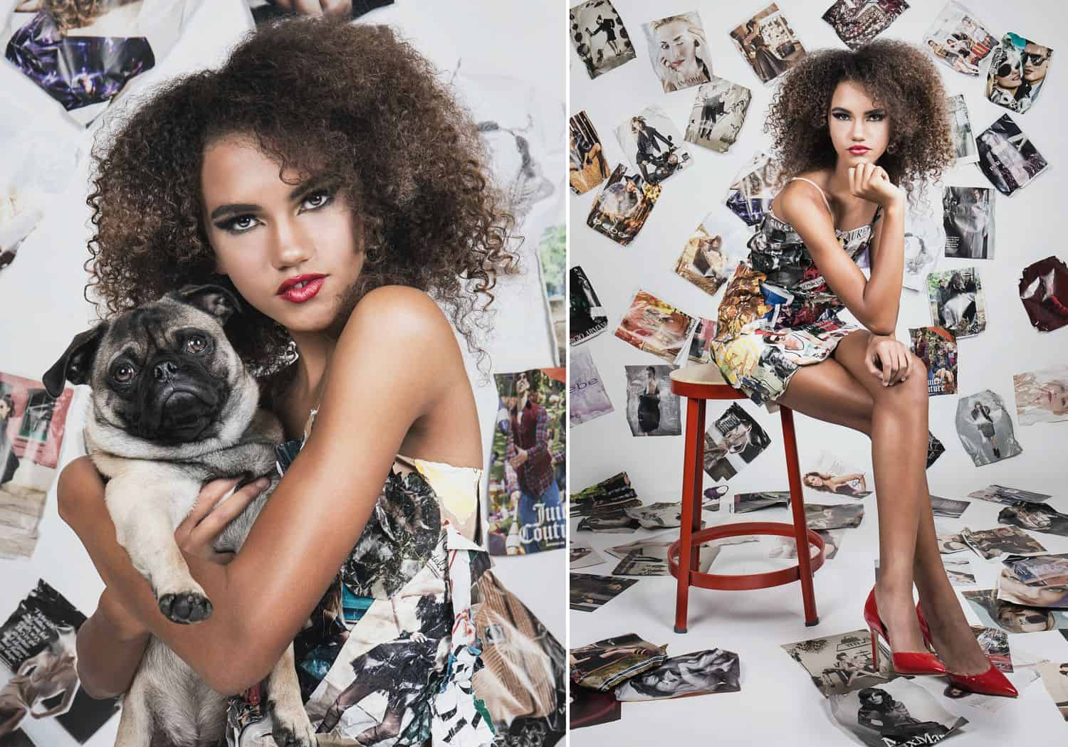 A Black model holding a pug dog poses on a red stool against a white wall plastered with photographs
