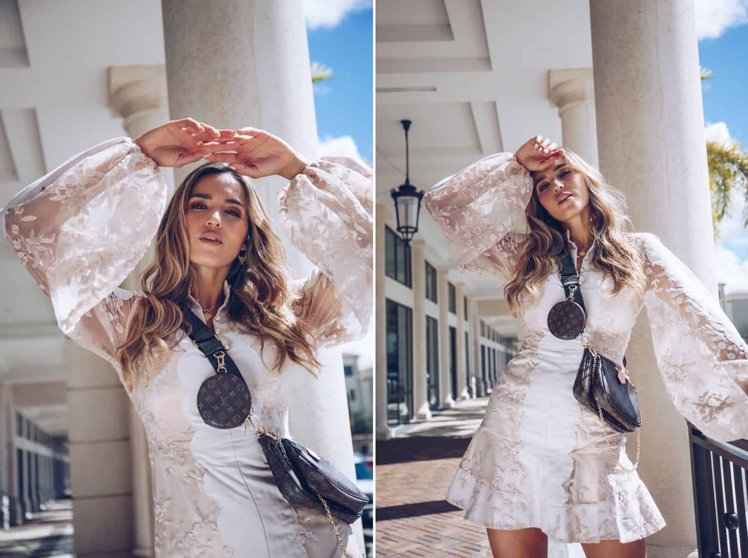 A model with long wavy hair and Louis Vuitton accessories poses outside against a towering white column