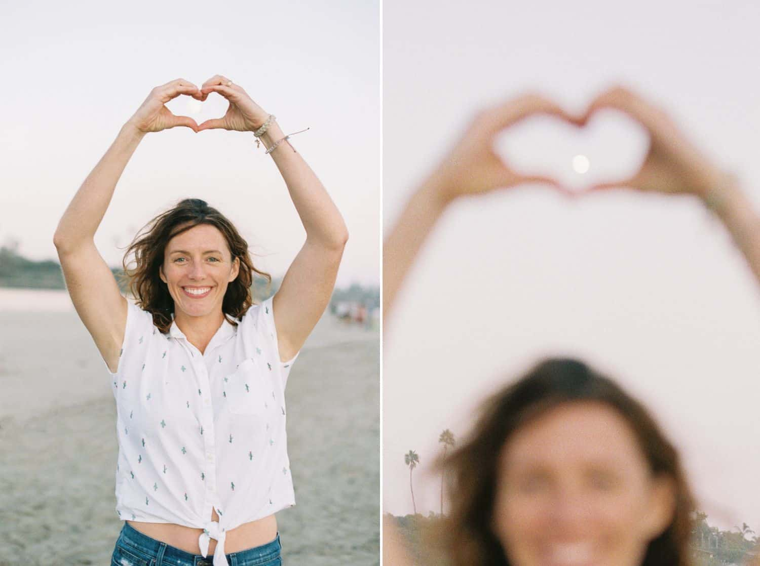 A woman on the beach makes a heart shape with her hands