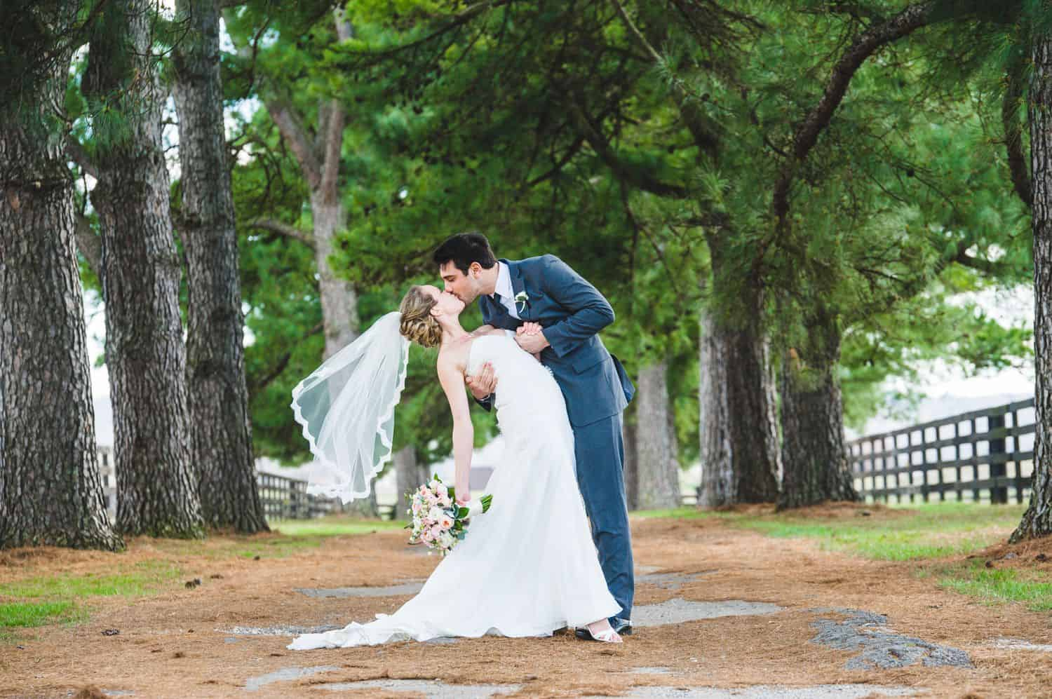 A groom dips the bride for a kiss in the shaded driveway of a mansion
