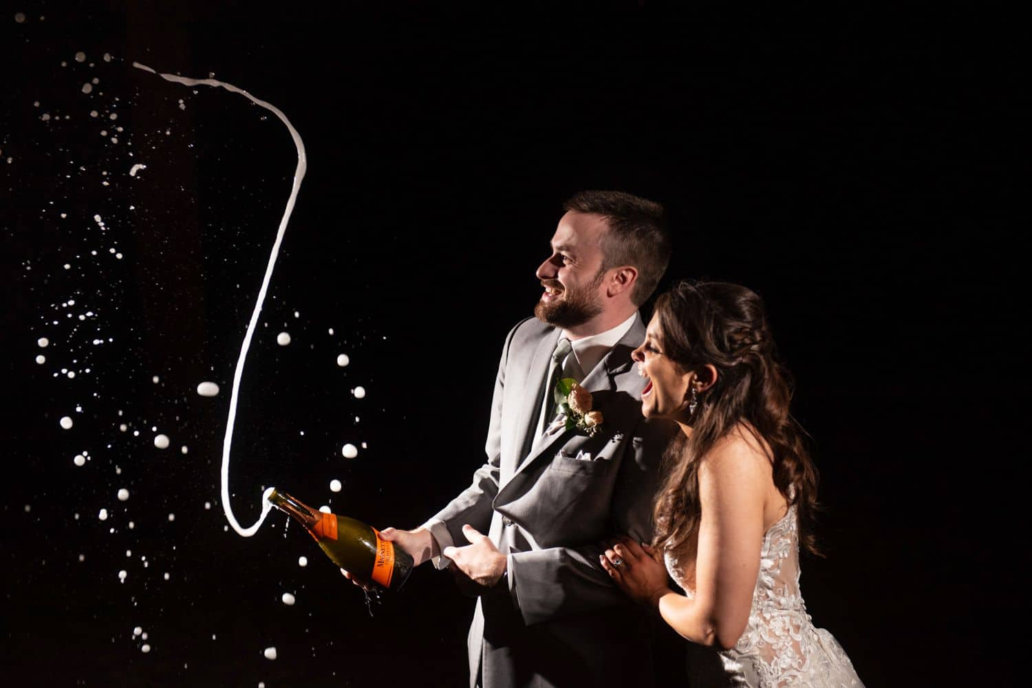 A bride and groom laugh as they pop a bottle of champagne