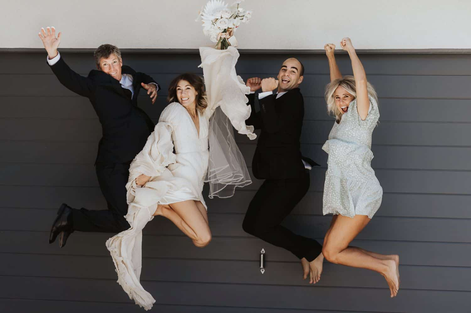 Family members jump in the air for a silly wedding day portrait