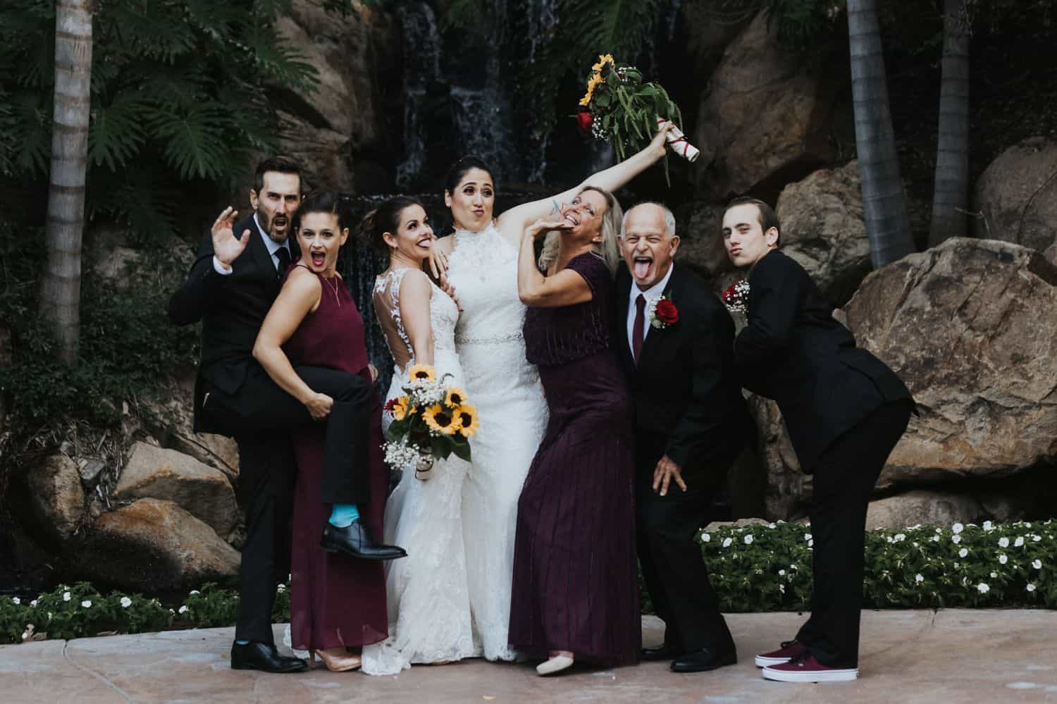 A family strikes a silly pose during their wedding day portrait