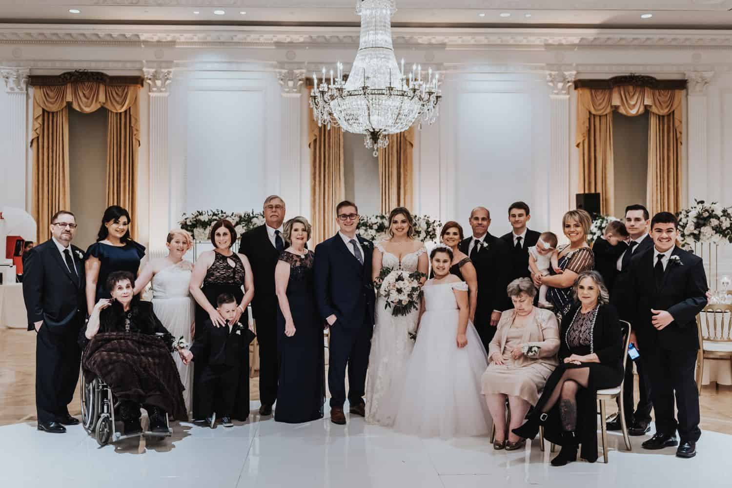 Large family grouping photographed at wedding with grandmother in wheelchair
