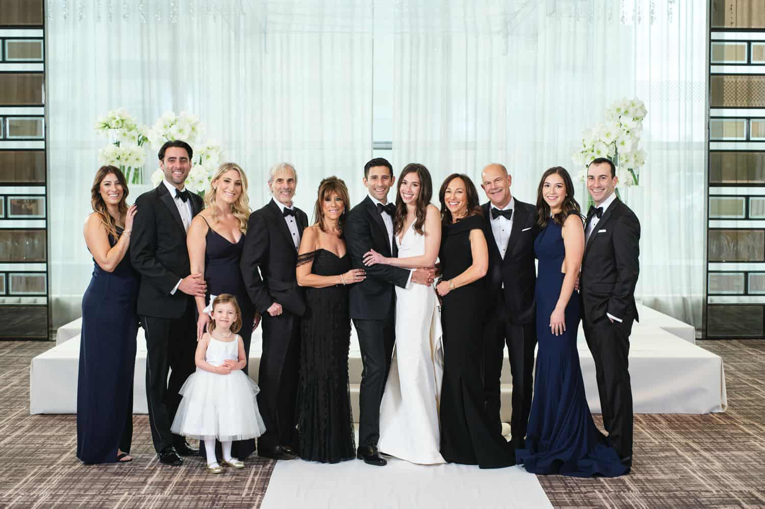 A large family poses in front of a white drape for a wedding day portrait