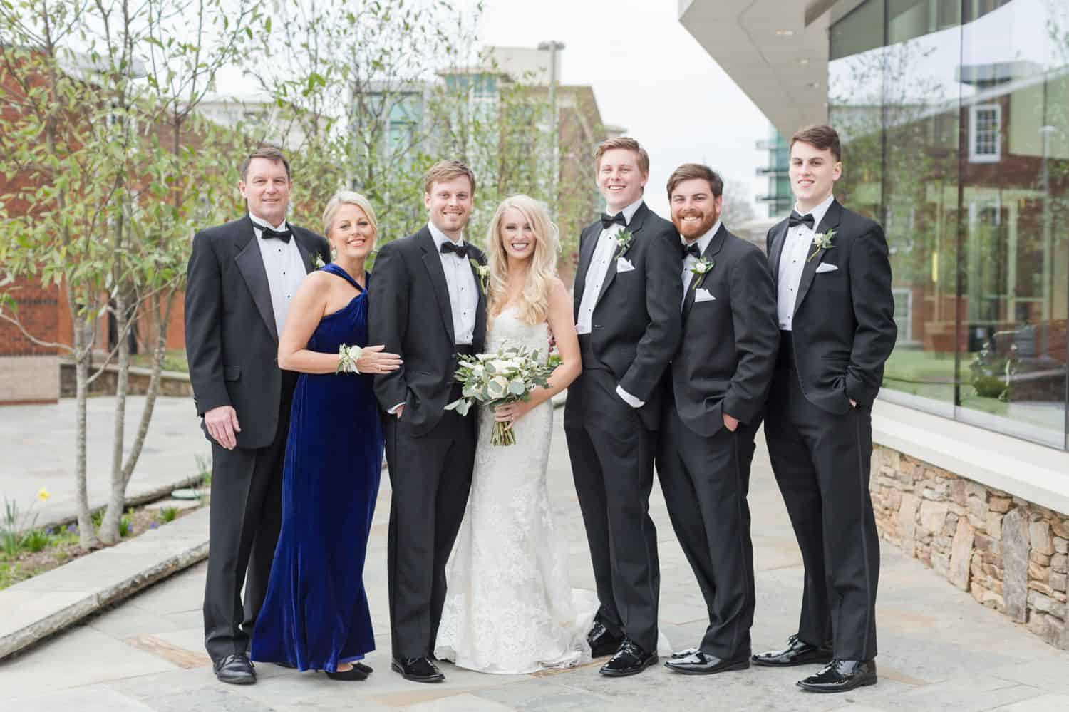 A bride and groom pose with family members for a wedding day portrait