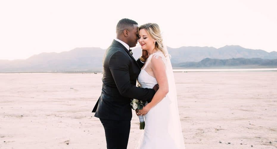 A Black groom pulls his White bride close in a tender desert portrait.