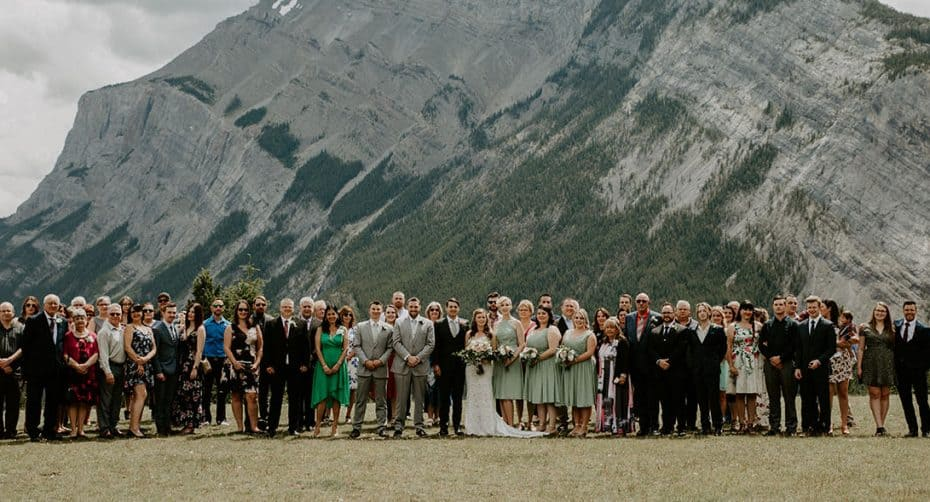 Large family portrait at a wedding in front of a mountain