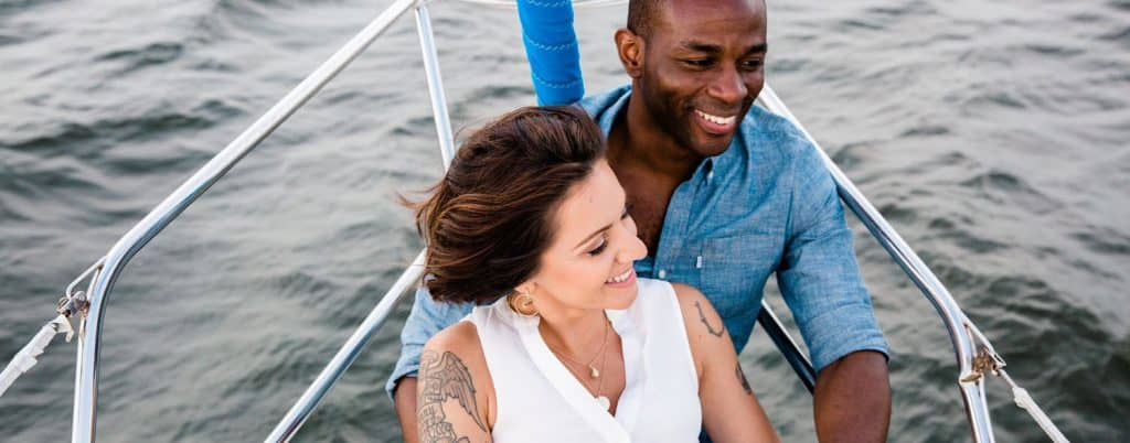 A man and woman smile while sitting close together on the bow of a sailboat