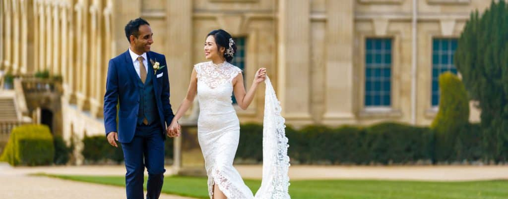 Bride and groom stroll through a mansion's garden