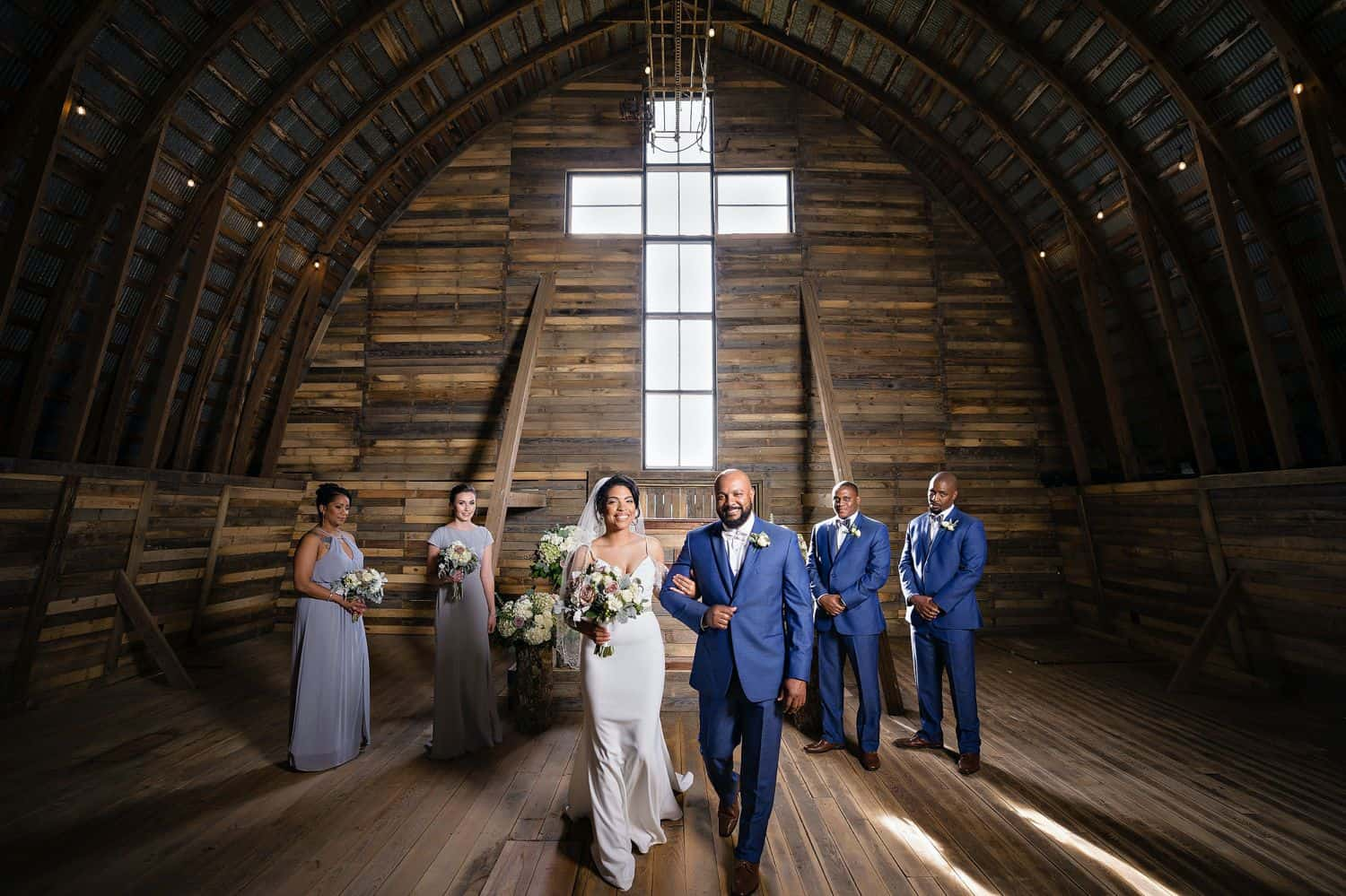 A wedding party stands by a cross-shaped window while the bride and groom process up the aisle at the end of their wedding