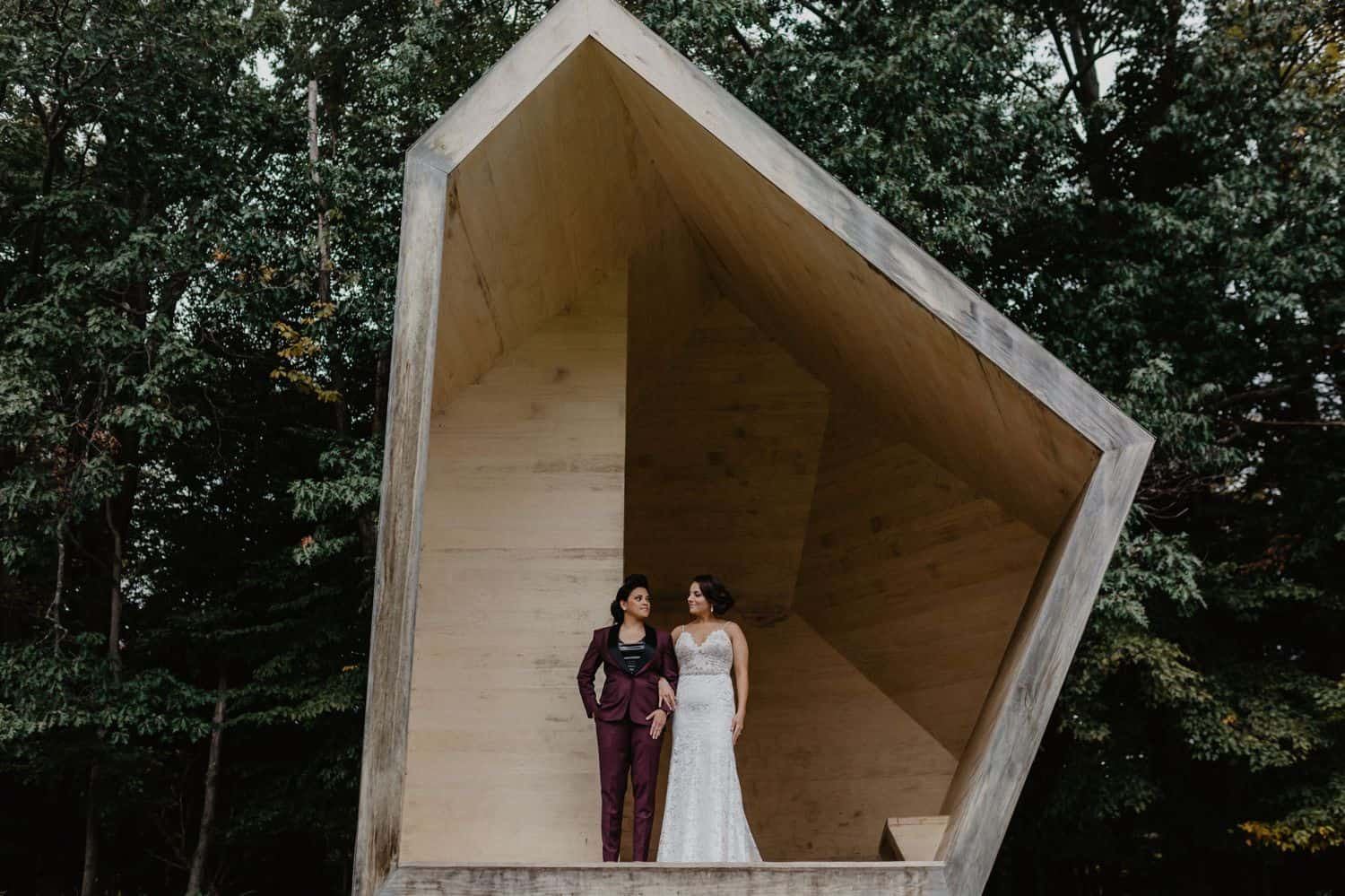 Two women stand in a geometric structure on their wedding day for portraits
