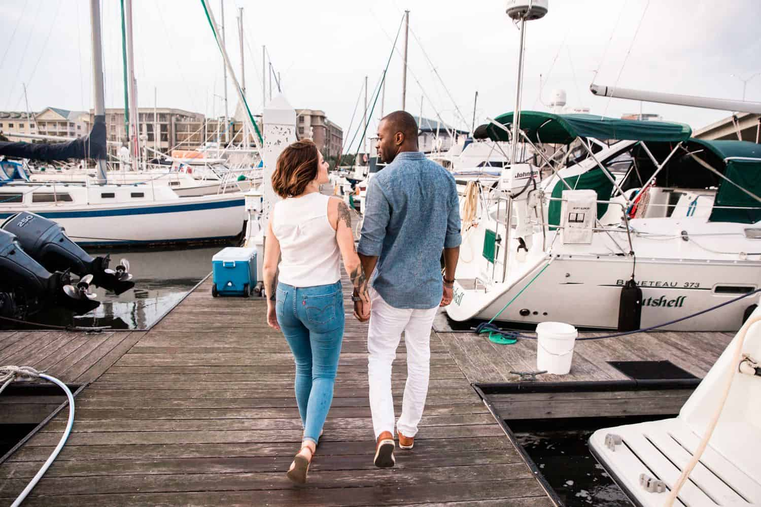 A man and woman walk along the dock of the bay with yachts and sailboats in the background.