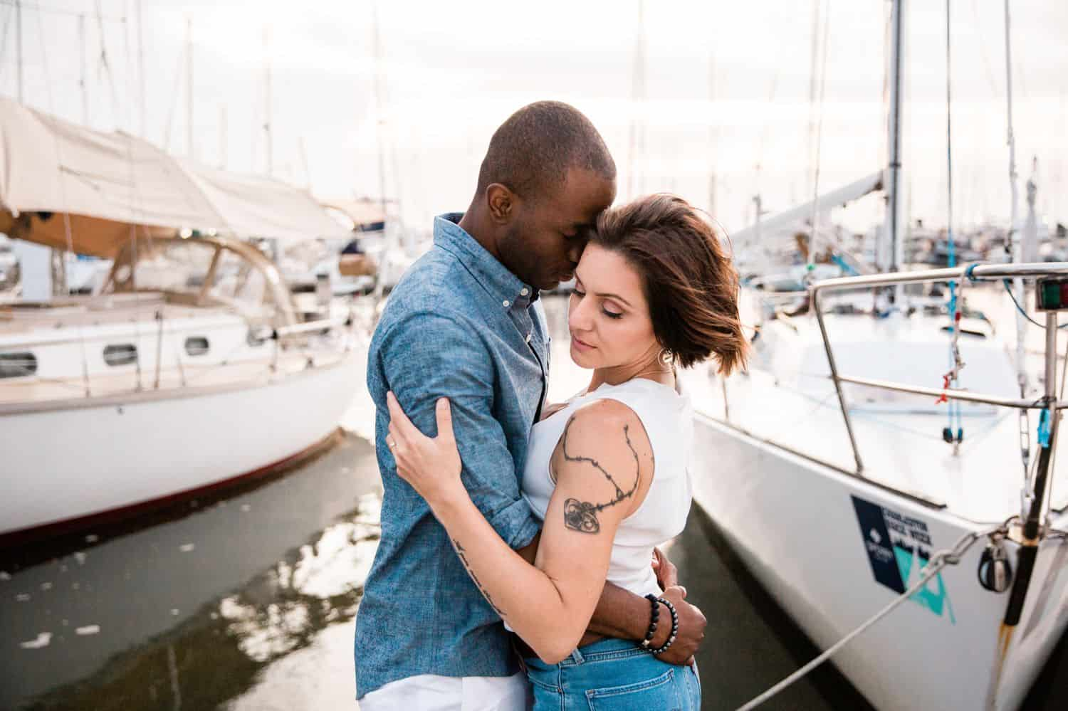 A Black man in a denim shirts and a White woman in a white shirt hold each other close on the dock of the bay