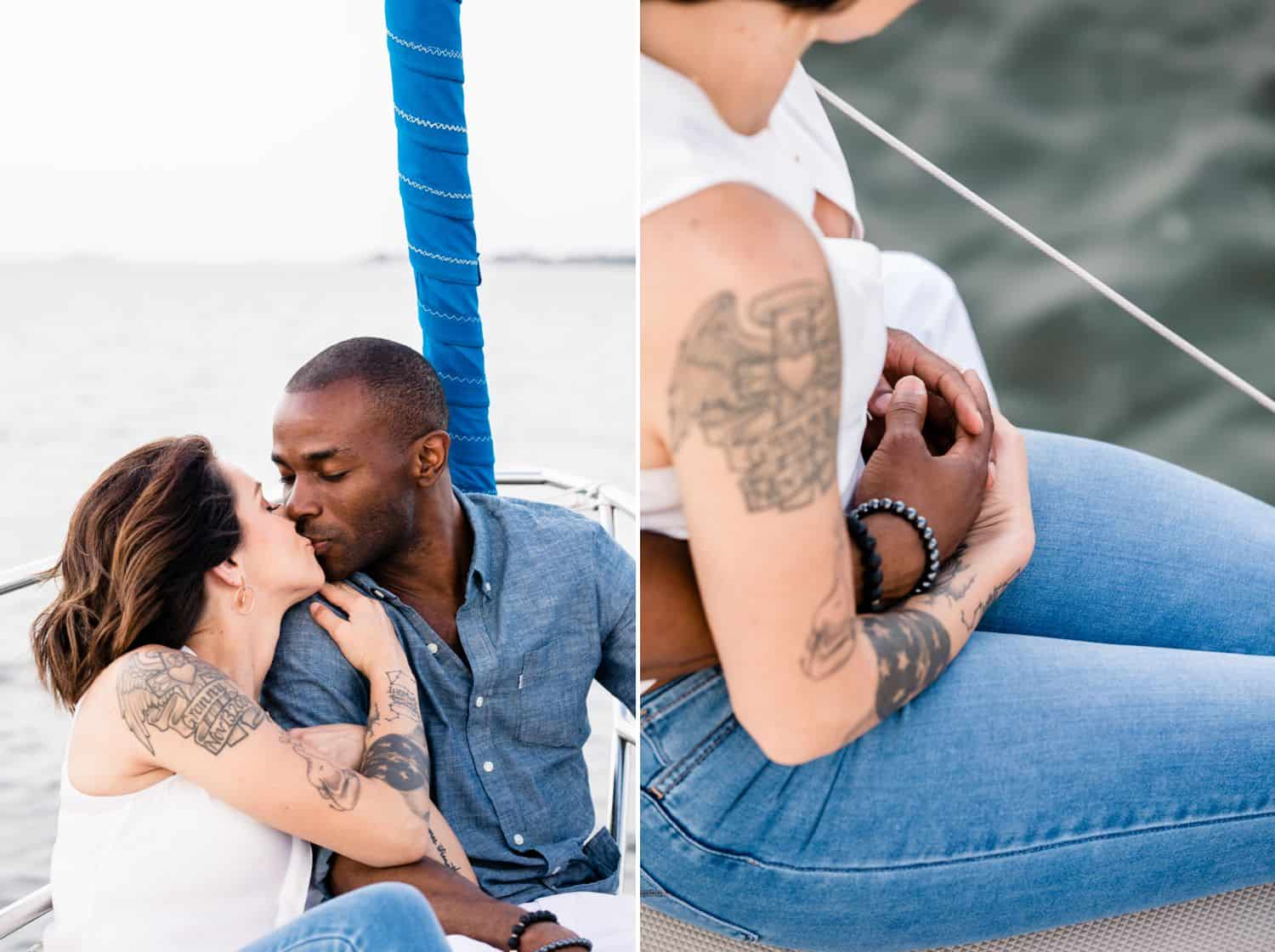A White woman sits on a sailboat kissing a Black man.