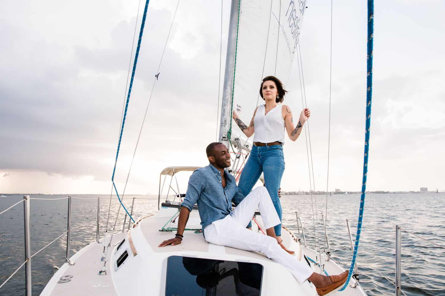 A Black man and a White woman sail on a sailboat