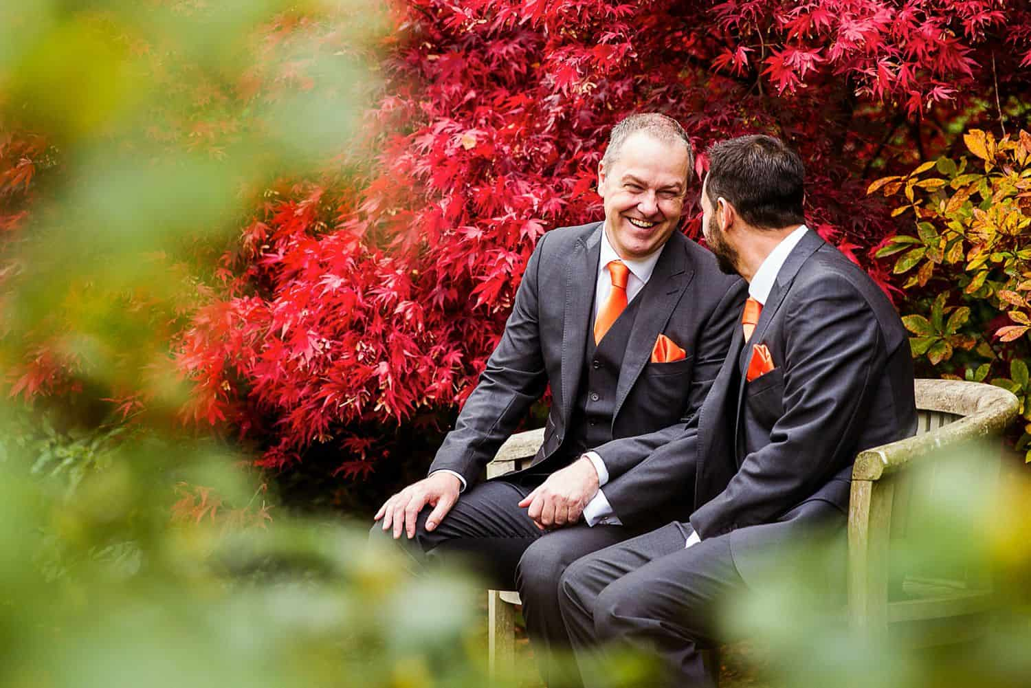 Two groomsmen sit on a bench in a church garden