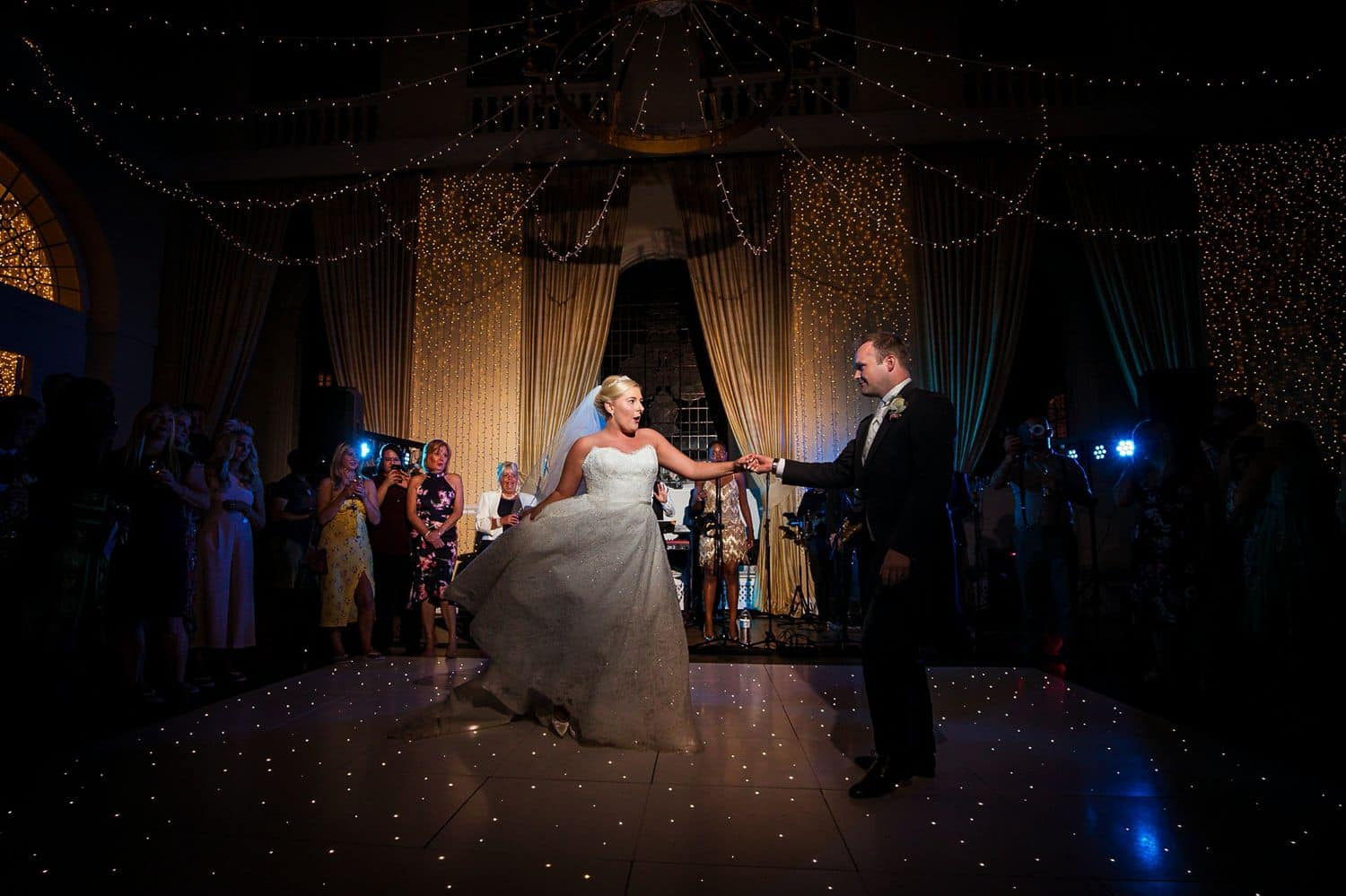 A bride and groom dance elegantly on a ballroom dance floor