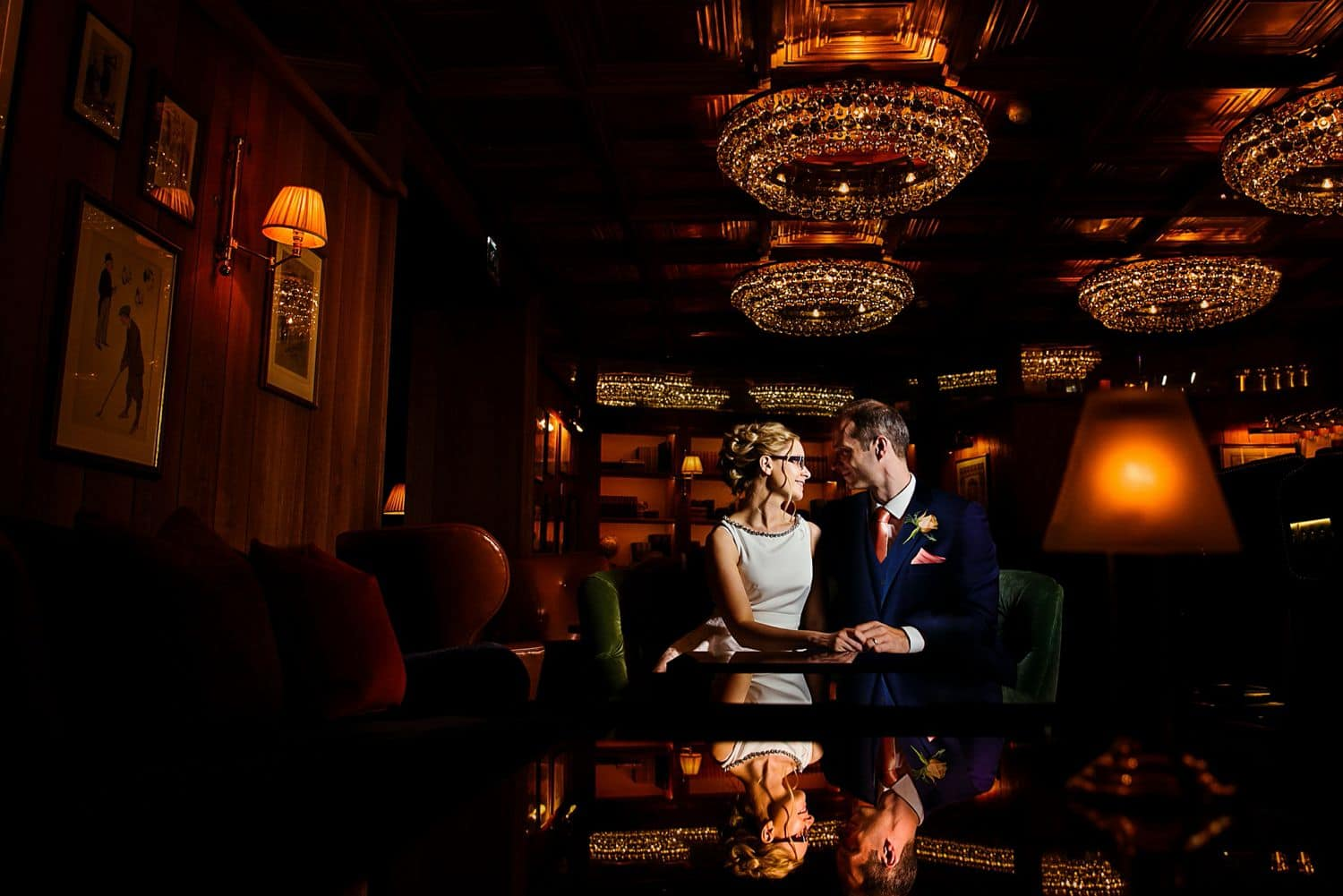 A bride and groom sit in a dark ballroom gazing into one another's eyes