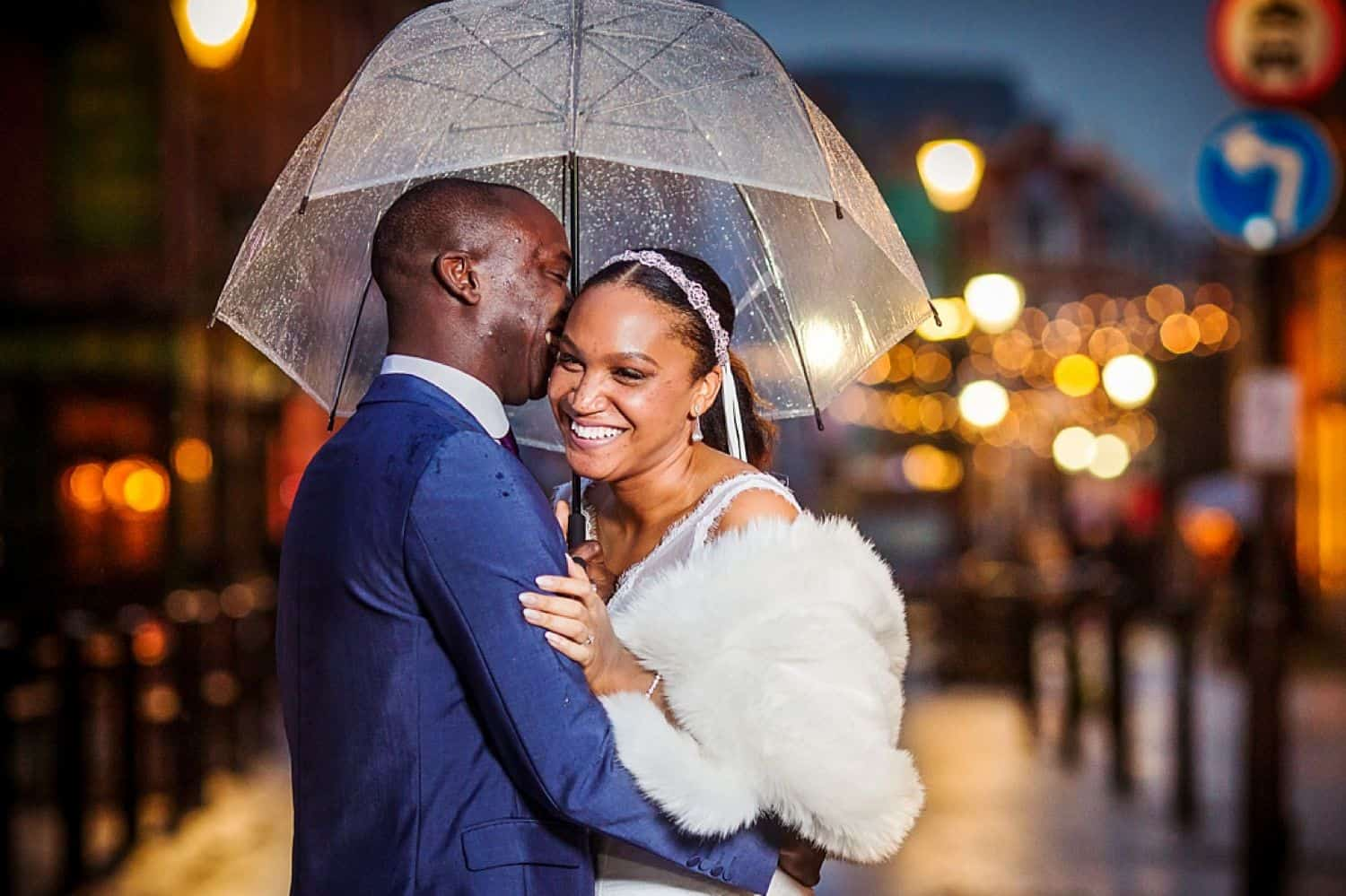 A groom in a blue tux hugs his bride in a white fur as they stand under an umbrella