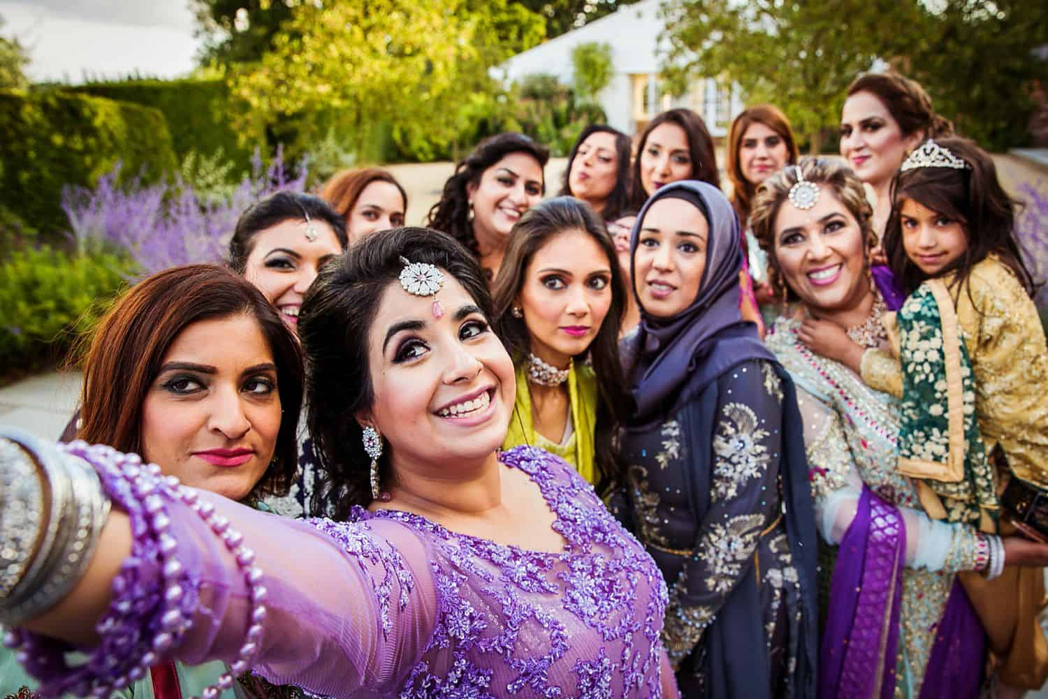 An Indian bride takes a selfie with her bridesmaids