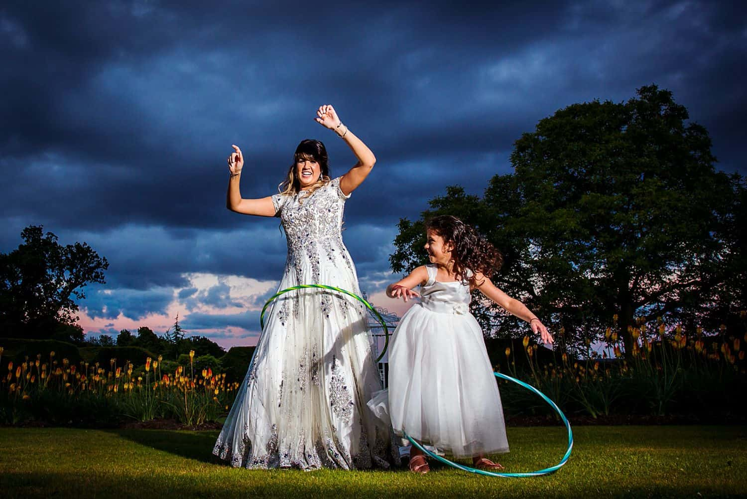 A bride and her flower girl twirl hula hoops at sunset