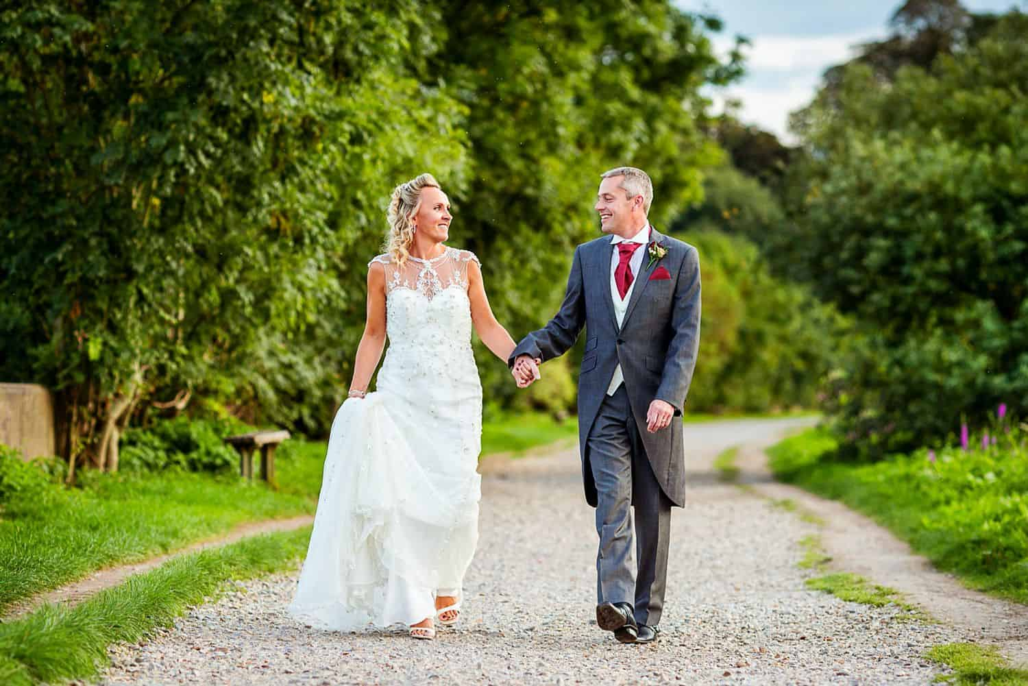 A bride and groom stroll outside down a garden path before their wedding