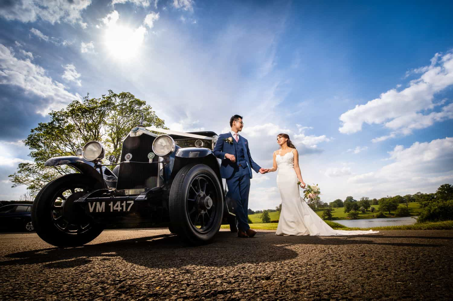 A bride and groom stand outside their getaway car on a bright sunny wedding day