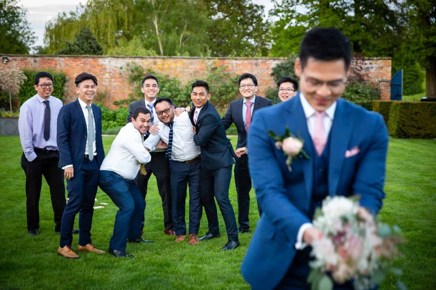 A groom holds a bouquet in a joking attempt to toss it to his groomsmen