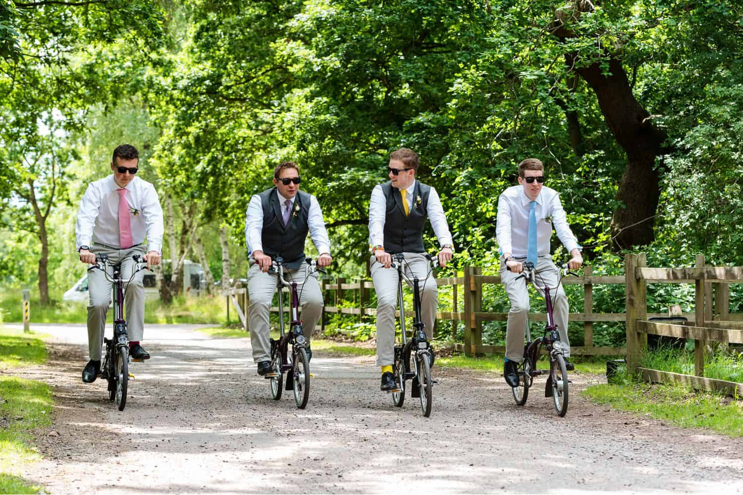 Groomsmen ride bicycles down a gravel path on the wedding day