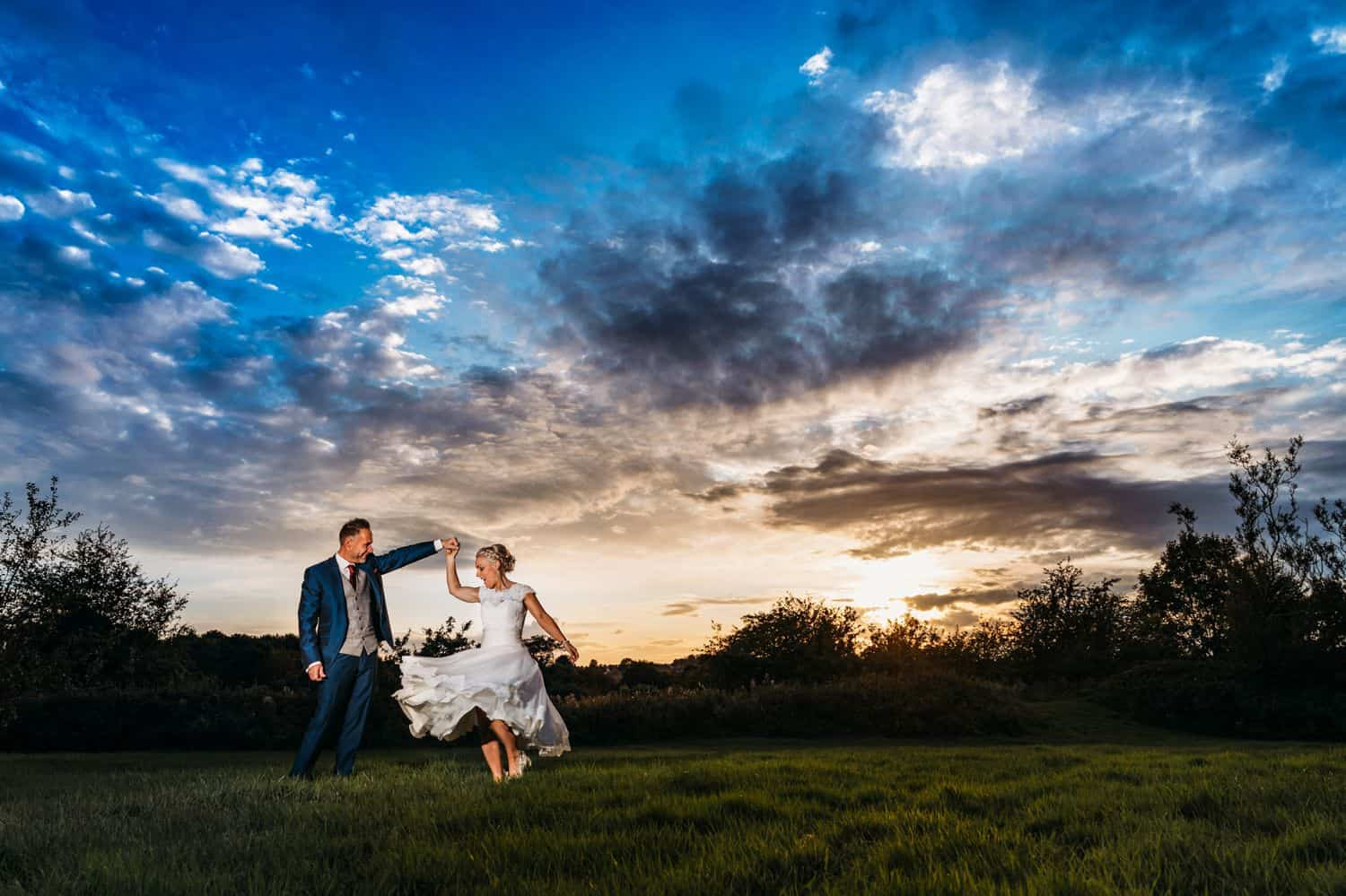 A sunset portrait of a groom twirling his bride in a wide lawn