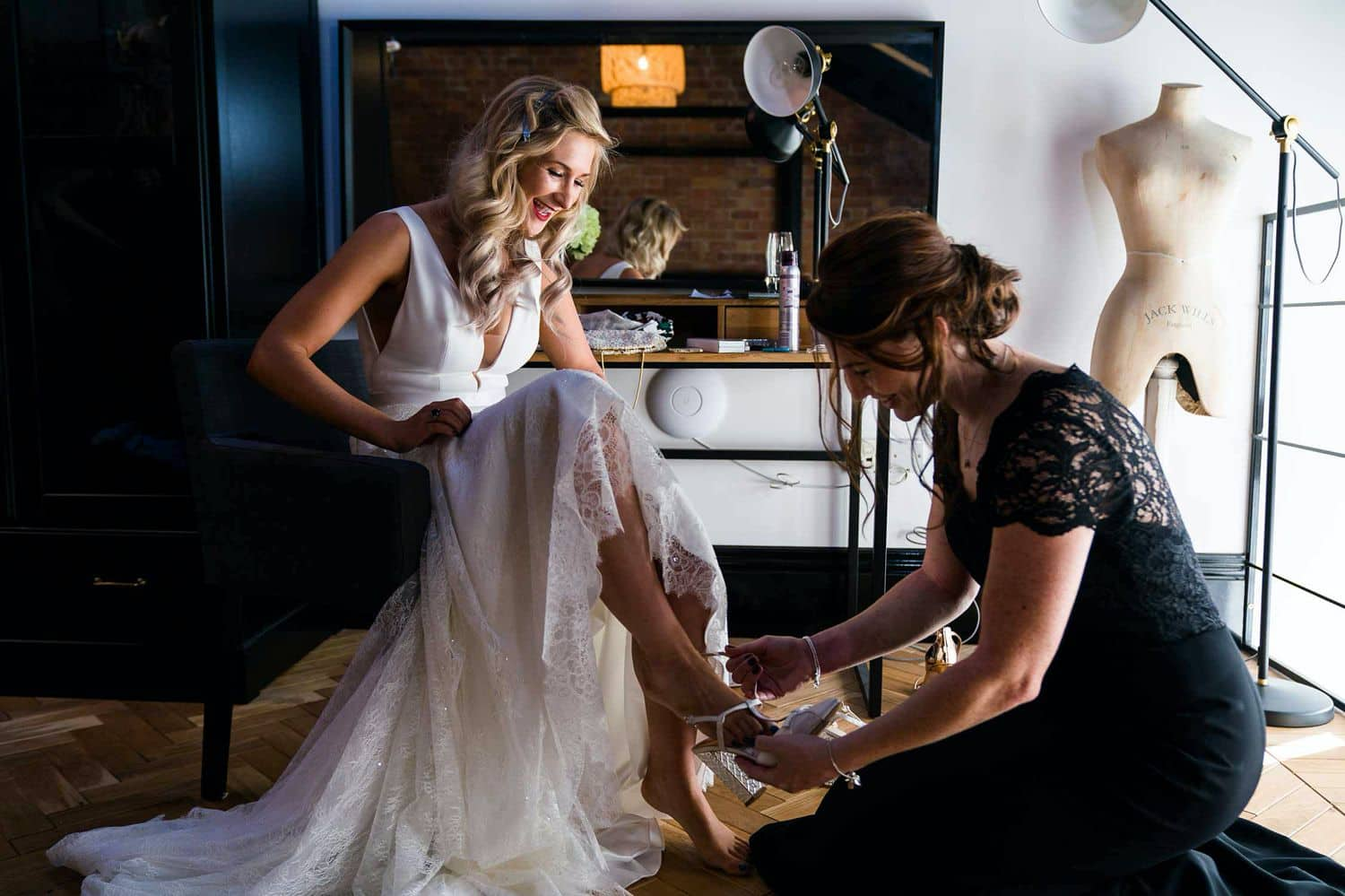 The mother of the bride helps her daughter put on her wedding shoes