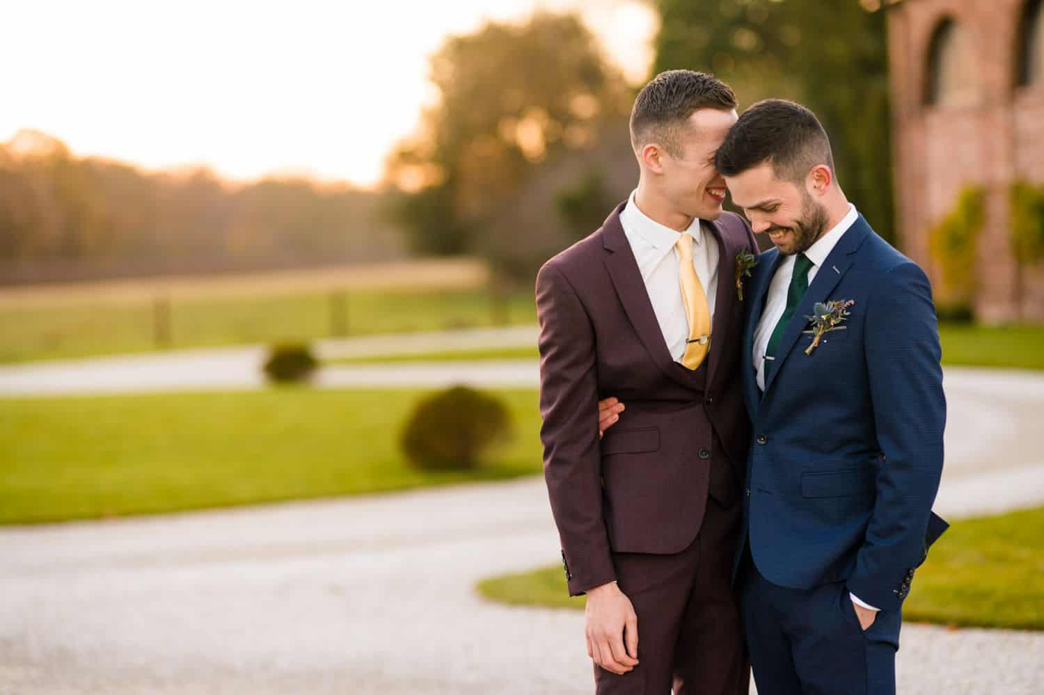 Two grooms snuggle close outside on their wedding day