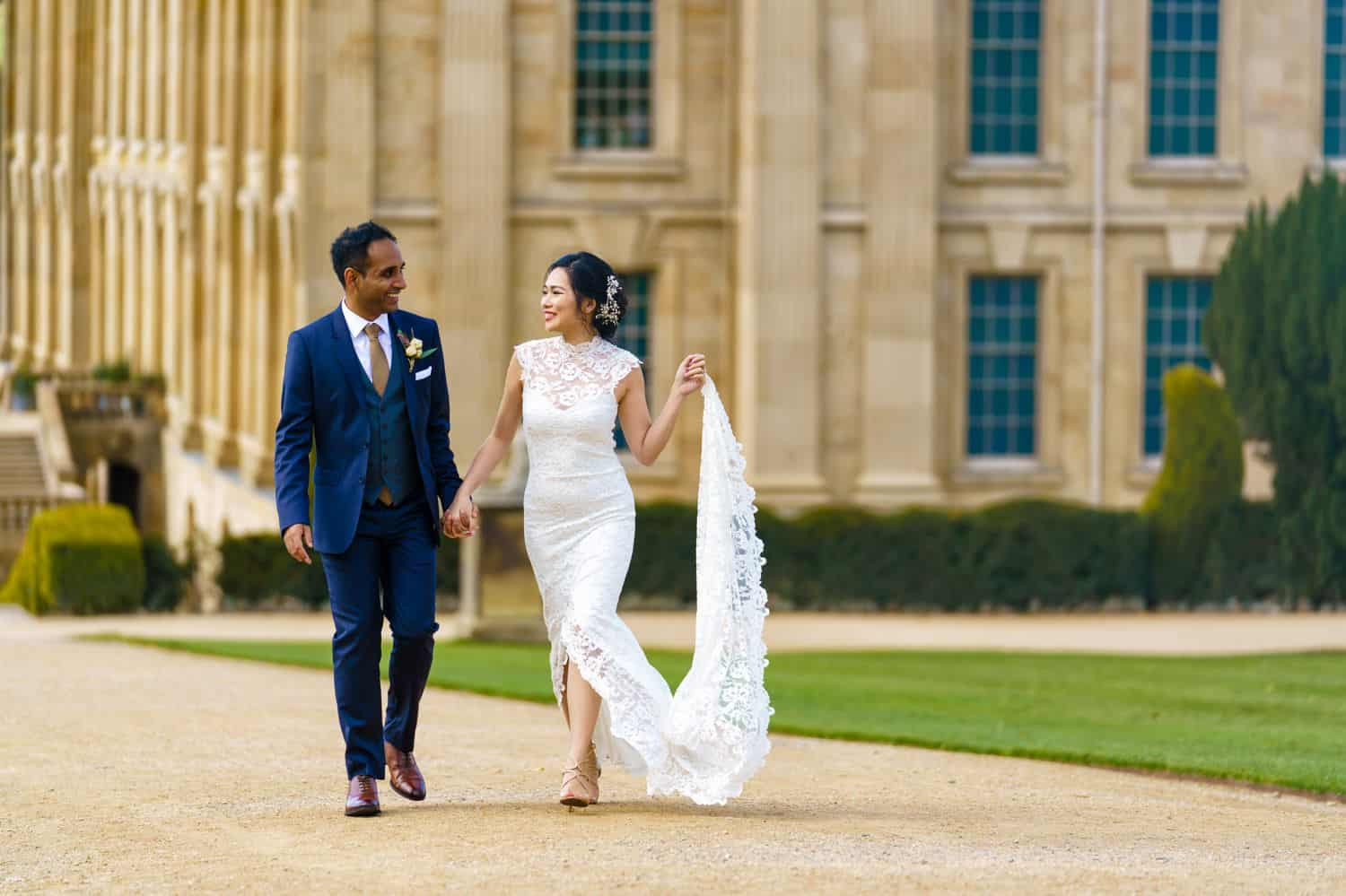 A bride and groom stroll down a garden path outside a luxurious mansion