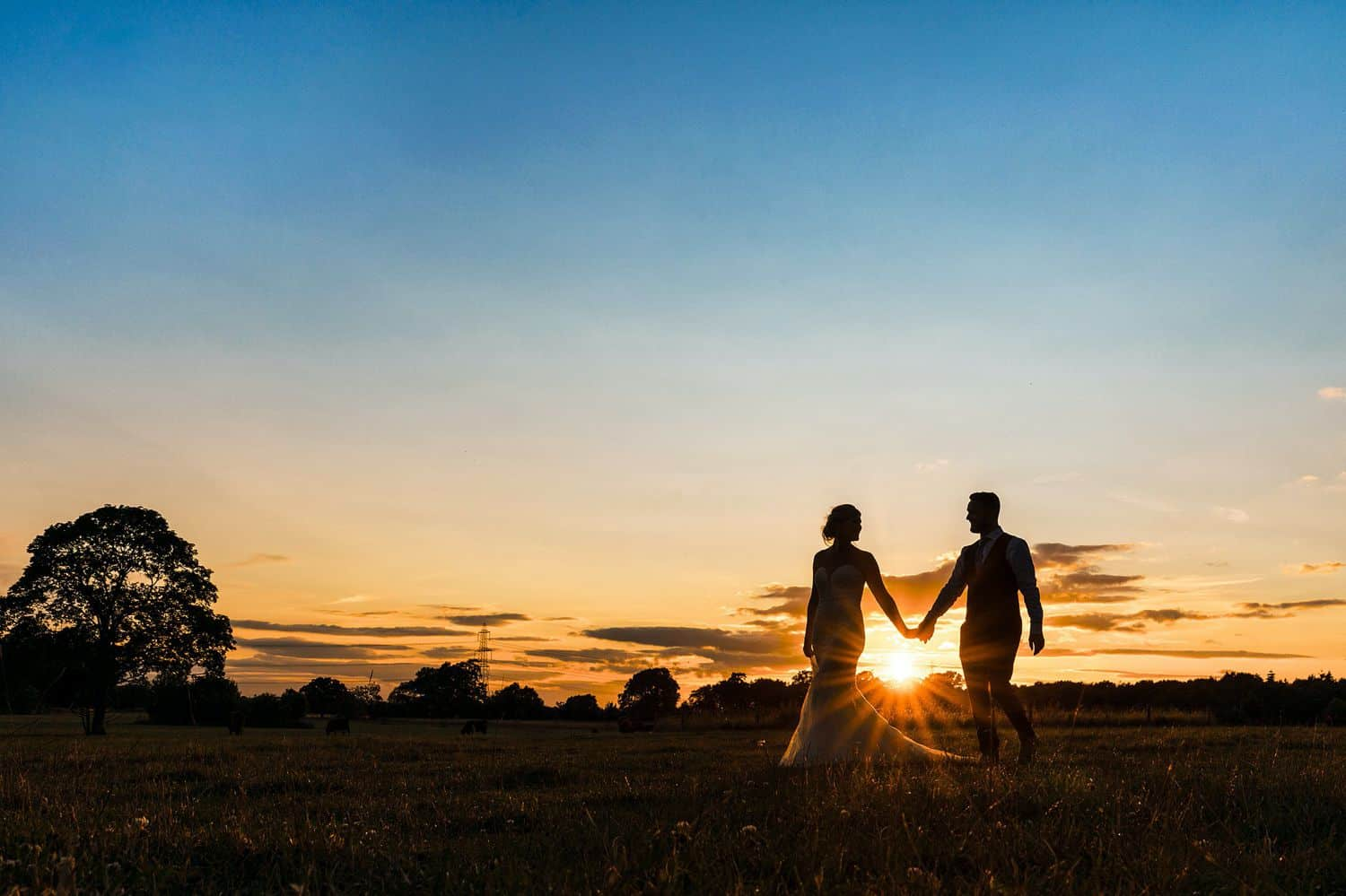 Silhouette of a bride and groom walking along the beach at sunset